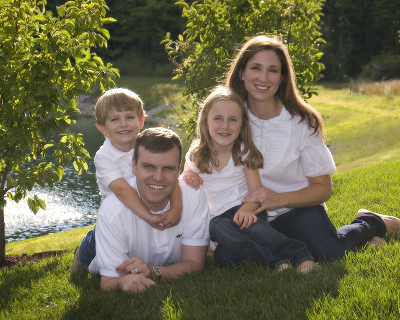 Portrait of young family laying in the grass by Dan Cleary of Cleary Creative Photography in Dayton Ohio