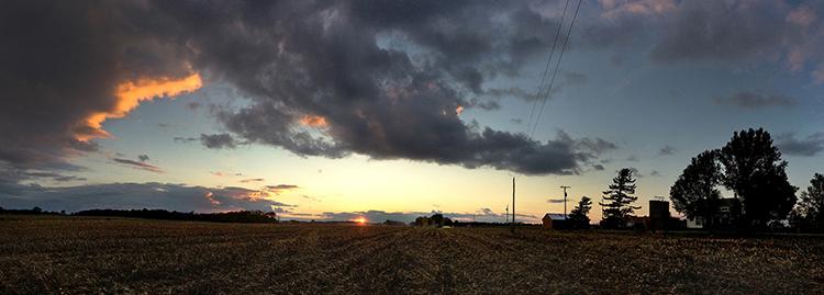 Panorama sunset fine art photograph of farmer picking corn near Bowling Green, Ohio