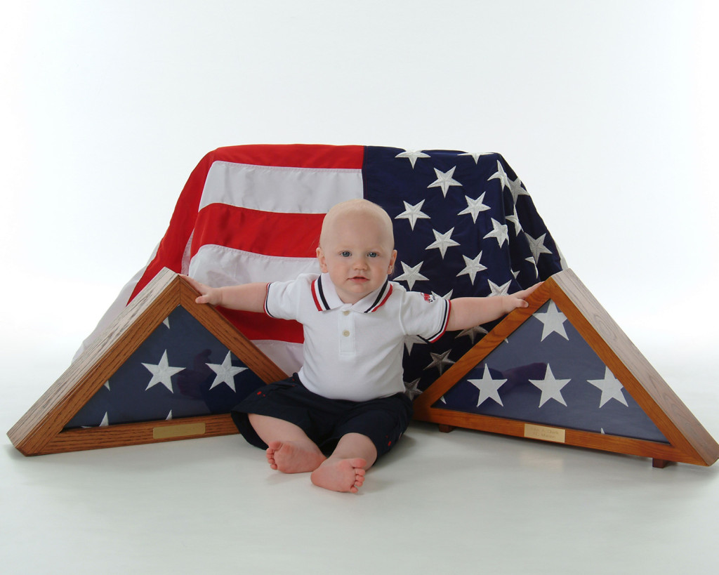 nine month baby boy portrait with grandfathers militay flags by Dan Cleary of Cleary Creative Photography in Dayton Ohio