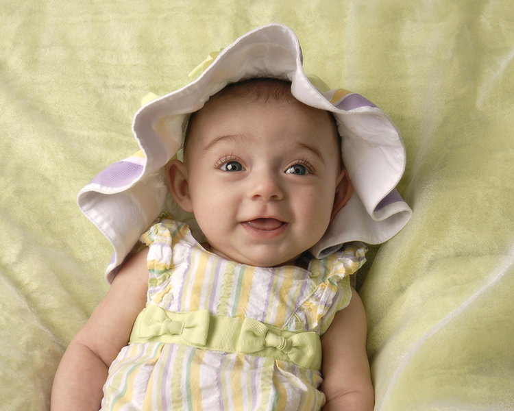 three month baby girl in hat with green background by Dan Cleary of Cleary Creative Photography in Dayton Ohio