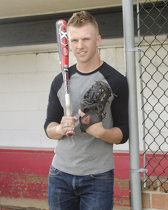 portrait of  High School senior boy in dugout with baseball bat and glove