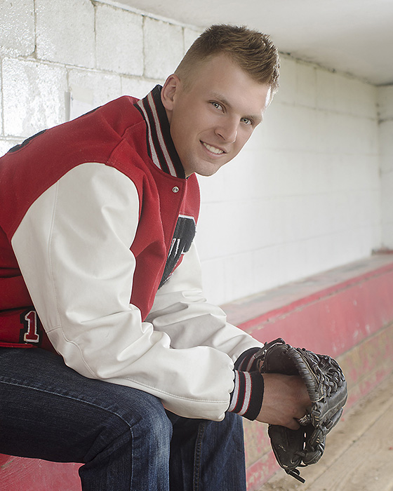 portrait of  High School senior boy in dugout with baseball glove