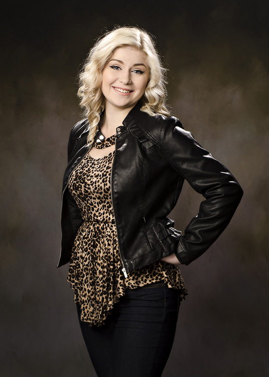 high school senior girl in a black leather jacket photographed in the studio against a dark background